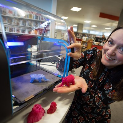 Picture of  a librarian holding examples of 3D printing models printed in a Scottish public library