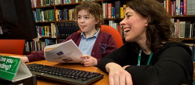 Librarian demonstrating coding to a school pupil during a Code Club session at Kirkaldy Library in Fife.
