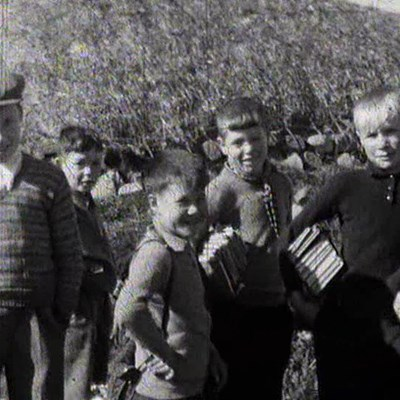 Black and White image of children from the Western Isles in front of a haystack, image is from the National Library of Scotland Moving Image Archive.