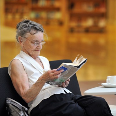 Senior citizen reading a book and drinking tea at The Mitchell Library in Glasgow