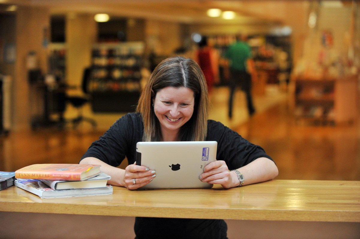 Library user using her own iPad at The Mitchell Library in Glasgow.