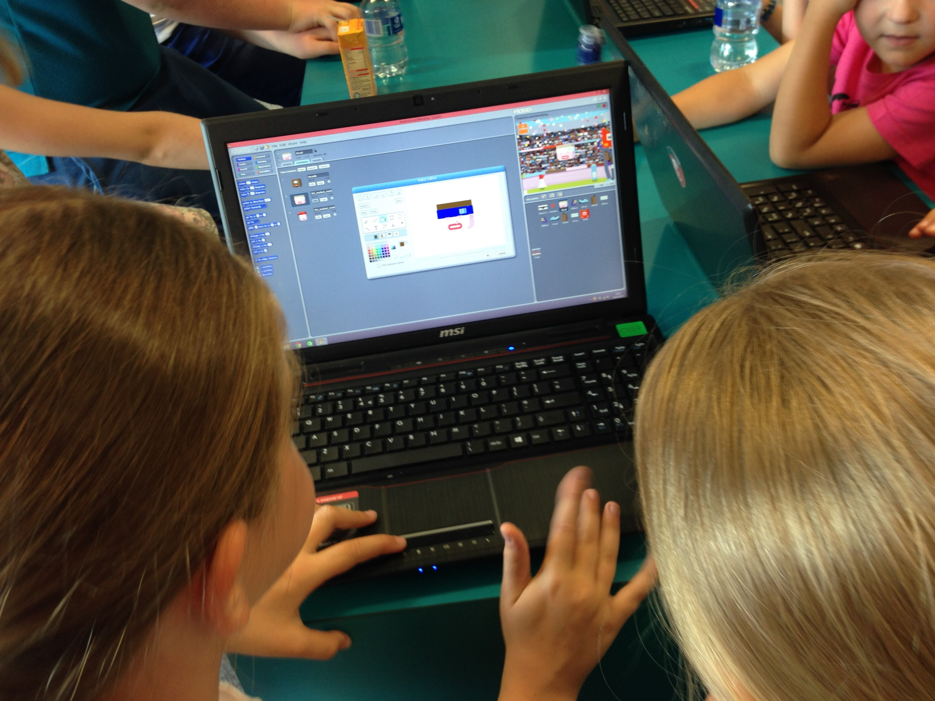 Children having a go at coding on a laptop during a library taster session in Glasgow, September 2014, enabled by the installation of WiFi.