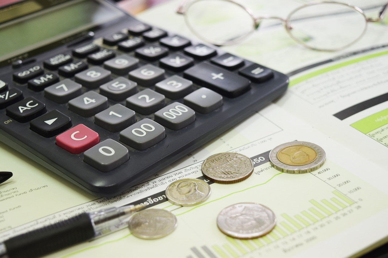 Calculator, money and spreadsheets lying on a table.